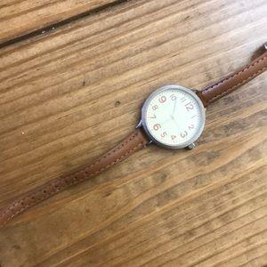 Accessories - Brown watch with thin wrist strap.